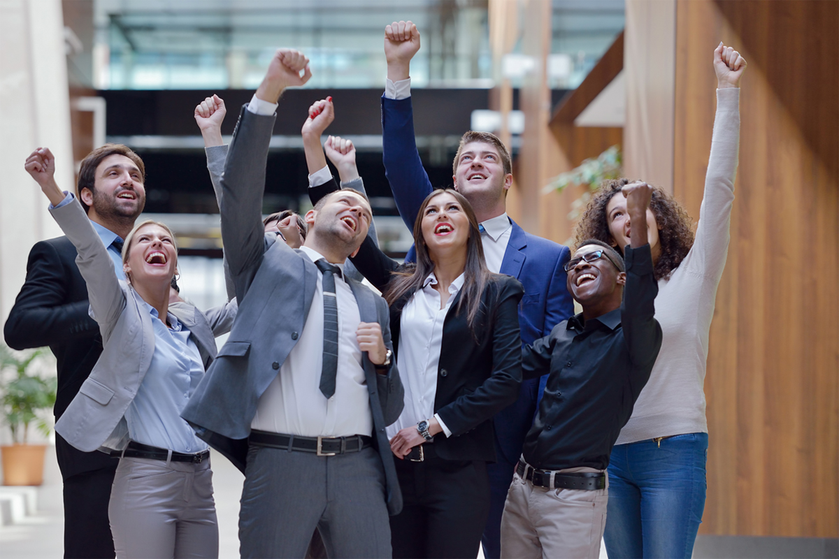 Group of excited employees with hands up